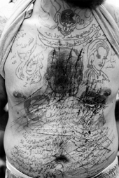 Moises Saman, Zacharia Gazmouth, a suspected Shabiha prisoner, his body covered in self-inflicted defaced pro-Assad tatoos, is a prisoner at a makeshift jail in the rebel-held town of Marae, Aleppo Province, Syria, July 24, 2012. (© Moises Saman / Magnum Photos)